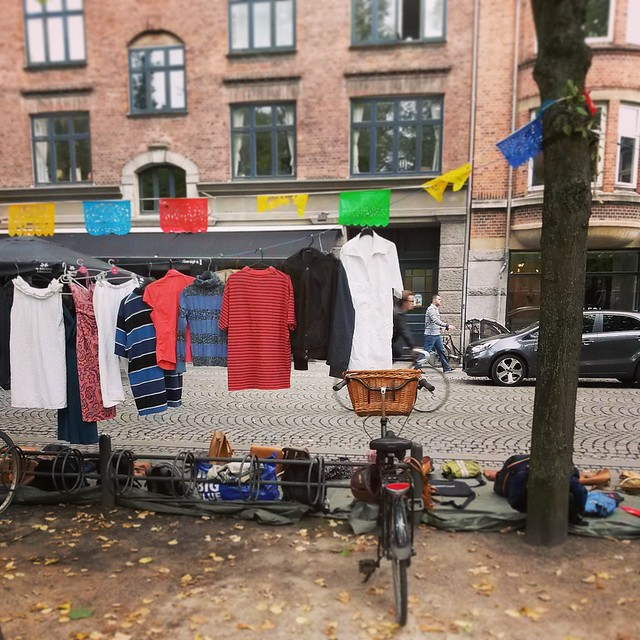 A bike parked at a vintage clothes stall