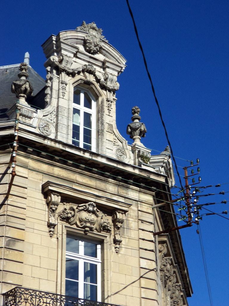 Angle brisé, pots à feu et fronton à guirlandes à l'angle des rues de Bouillé et Eugène Tessier