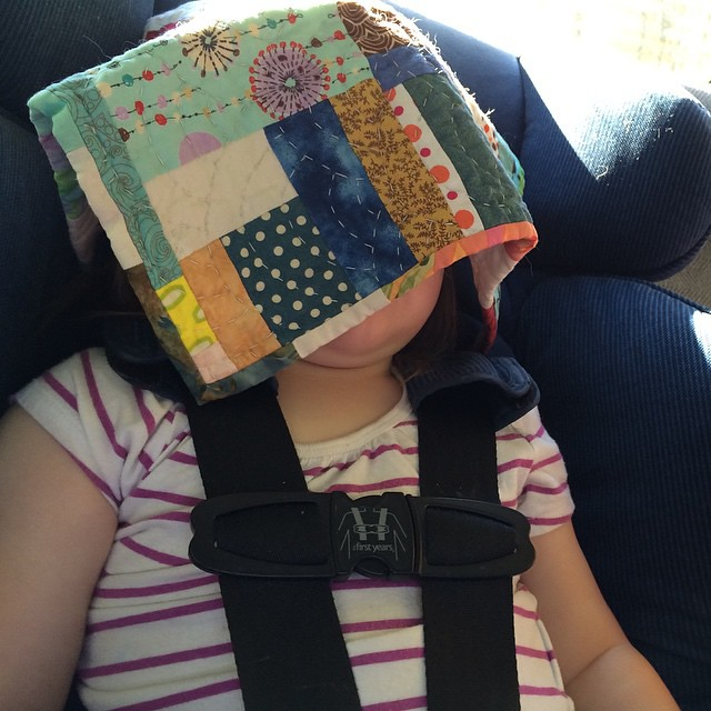 Taking a car nap (with a @cauchycomplete scrappy mini-quilt to shade her eyes).