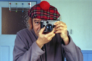 Reflected self-portrait with Corfield Periflex camera and tartan hat