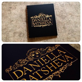 Custom illustrator portfolio book with engraved color fill treatment in gold on matte black acrylic