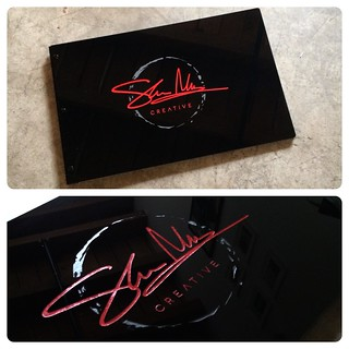 Custom graphic design portfolio with engraved color fill treatment on glossy black acrylic