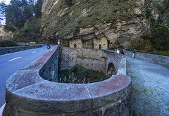 Houses in the cliff along sharp curvy bridge at Via Mala