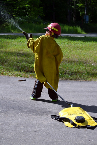 A youngster from Detroit dons an oversized firefighter's shirt to experience what is might be  like on a firefighting team. (U.S. Forest Service)