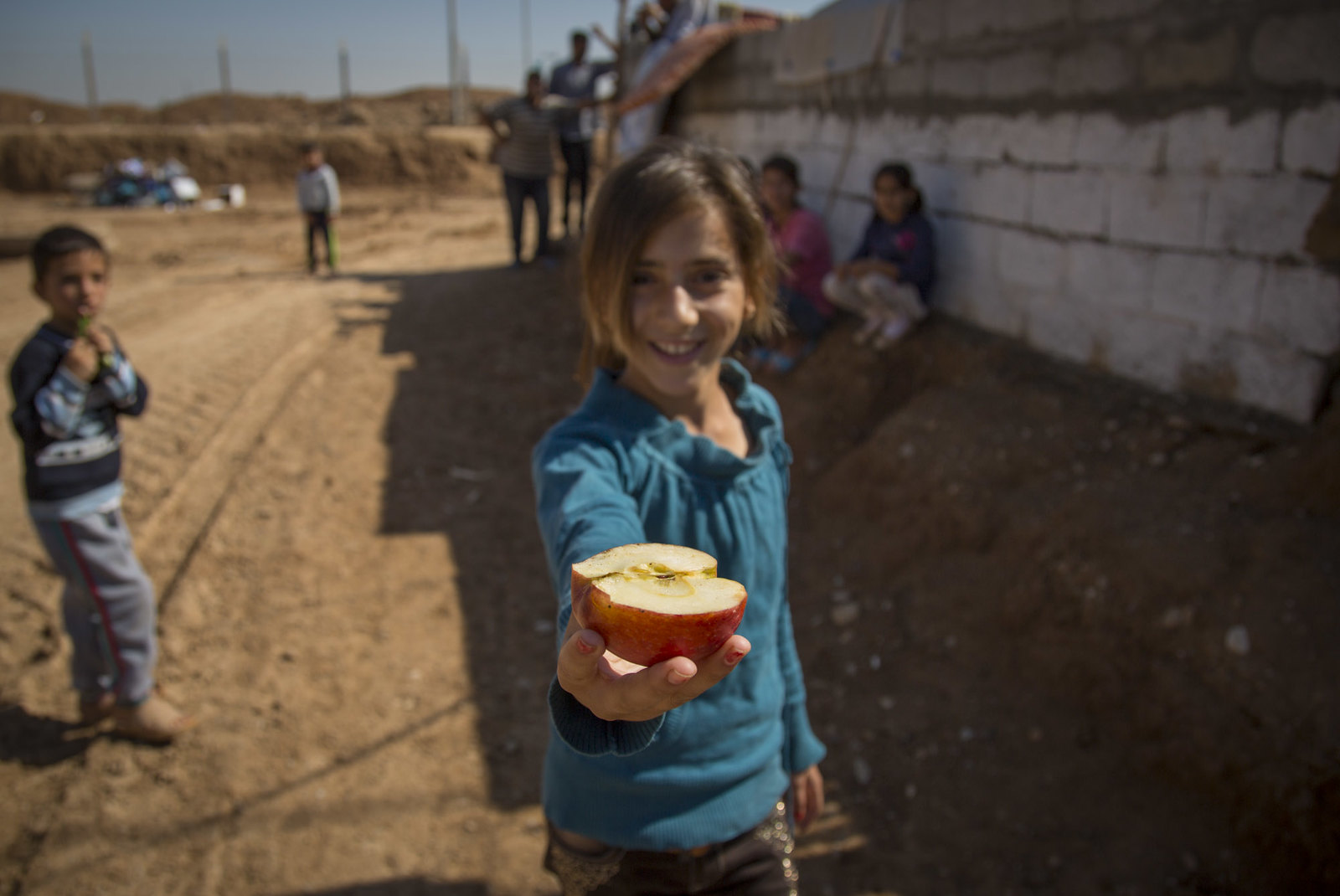 A Young Syrian Refugee Girl Sharing An Apple, Qushtapa Refugee Camp, Erbil, Kurdistan, Iraq