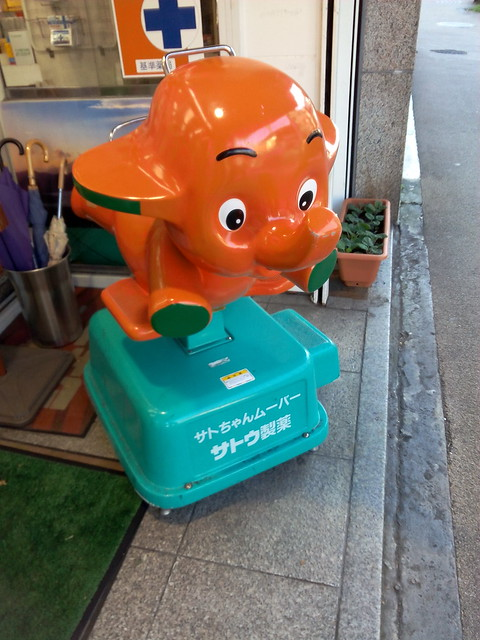 Japanese pharm companies have mascots, and dolls and rides are placed at pharmacies