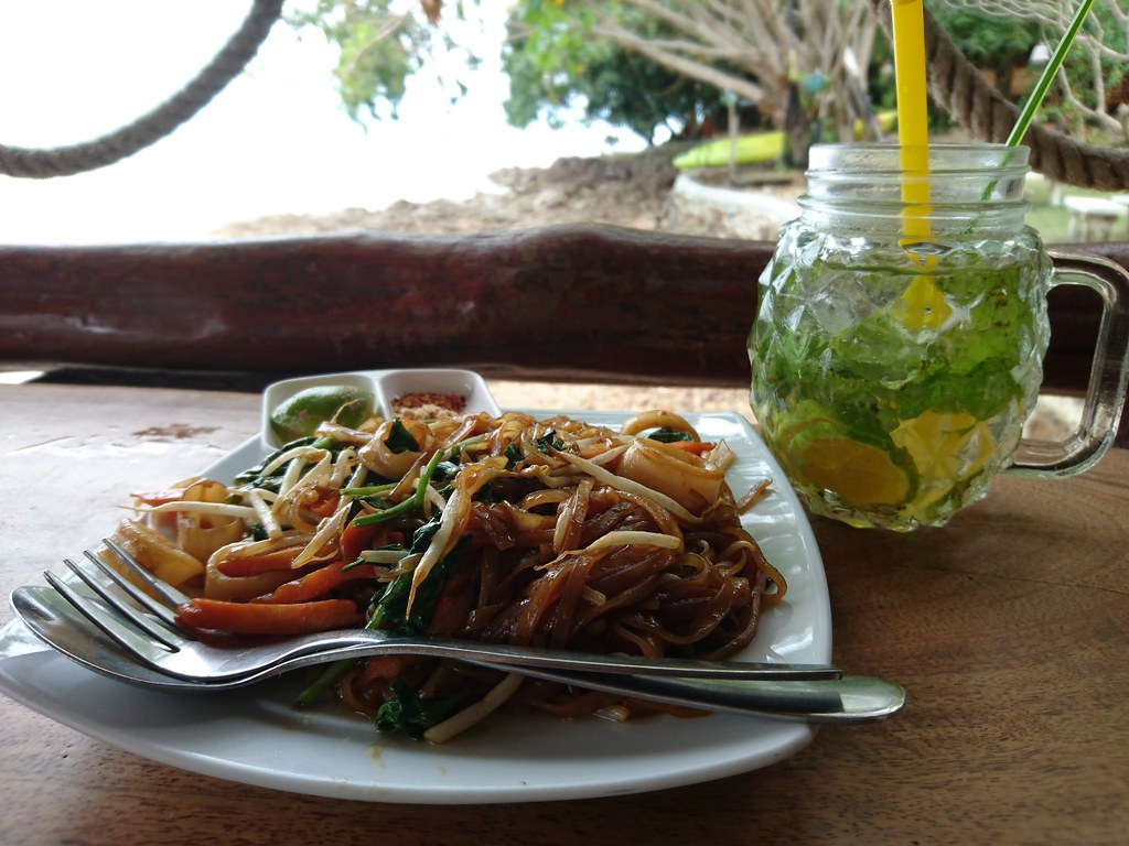 Fried noodle with squid and some water with mint and lime, overlooking the sea at Sabai Corner