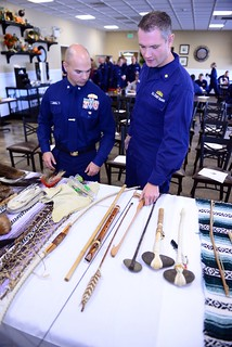 Cmdr. Joe Meuse, executive officer of the U.S. Coast Guard Training Center, and Lt. Cmdr. Doug Daniels, staff judge advocate for the training center, look over some Lenape Indian tribe artifacts during a Native American Heritage event held Nov. 5, 2014. Coast Guard members were invited to see the displays and listen to Wesley Dunn, vice president of the Museum of Indian Culture, give a speech about the Lenape's history in the region. (U.S. Coast Guard photo by Chief Warrant Officer John Edwards)
