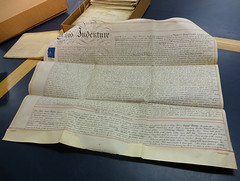 "A large sheet of thick yellowish paper closely covered in handwriting.  The heavily-embellished words ""This Indenture"" are visible in the top left-hand corner.  In the background is a box containing similar sheets of paper, these ones folded up."