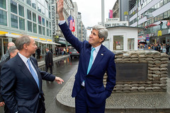 U.S. Secretary of State John Kerry waves to office workers looking through their window at him as he visits Checkpoint Charlie while touring Berlin, Germany, on October 22, 2014, following an event to commemorate the 25th anniversary of the fall of the Berlin Wall, and before holding a bilateral meeting with German Chancellor Angela Merkel. [State Department photo/ Public Domain]