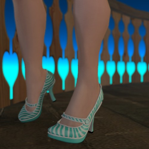 Image Description: Close up of legs in teal and white heels in front of a wooden fence with hearts carved into the slats.