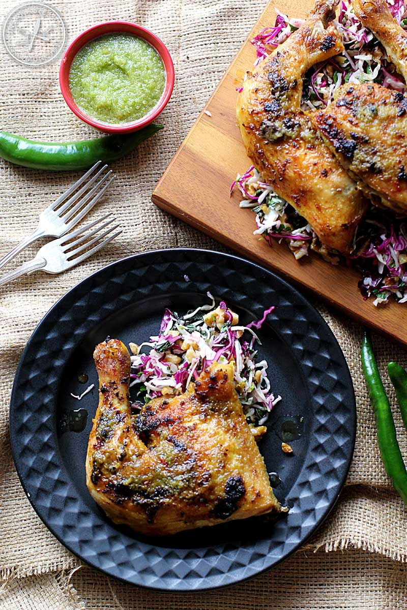 Yuzu peri peri chicken is pictured here both on a board/platter, and in an individual serving on a black plate with a textured rim. Served with a herb and mixed cabbage salad.