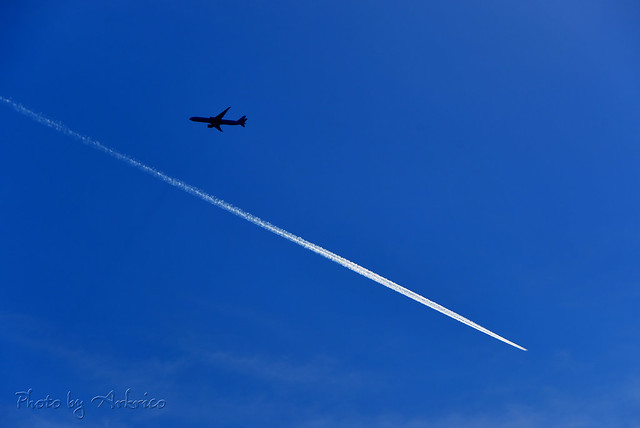 A silhouette and a contrail