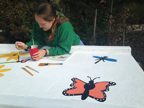 Image of a volunteer painting a monarch butterfly on a storm drain.