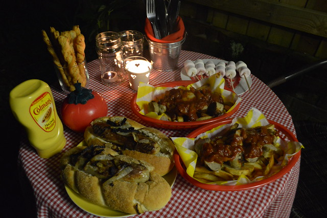 This is a picture of food on bonfire night, currywurst, hotdogs and mulled wine.
