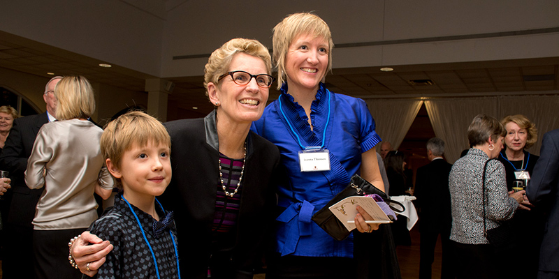 At the celebratory Installation dinner for our 14th Chancellor, Jim Leech: Premier Kathleen Wynne with Jim's grandson and daughter, Cedar and Dr. Joanna Thiessen. (Photo: Stephen Wild)