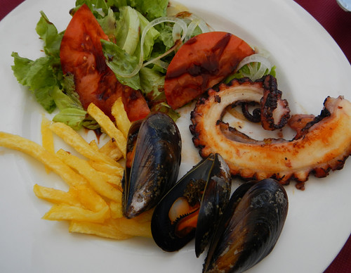Having a lunch of pulpo (octopus), mussels, salad and fries at a seaside café on Spain's Galician coast