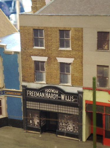 "A model of a three-story terraced building with a ground-floor shopfront reading ""Footwear / Freeman, Hardy and Willis Limited""."