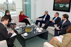 German Chancellor Angela Merkel and her staff sit with U.S. Secretary of State John Kerry, U.S. Ambassador to Germany John Emerson, State Department Deputy Chief of Staff Jon Finer, and Deputy Assistant Secretary of State for European and Eurasian Affairs Julieta Valls Noyes at the outset of a bilateral meeting at the Chancellery in Berlin, Germany, on October 22, 2014. [State Department photo/ Public Domain]