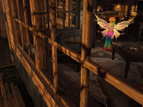 Image Description: Long distance view through a sunlit window of a brown-hued parlor with a faerie in a rainbow dress standing inside of it.