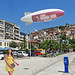 Greece, Macedonia, Kavala, girl in yellow, & an advertising blimp at the harborfront