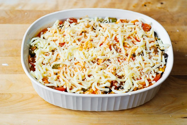 Sprinkle the enchilada casserole generously with shredded Mozzarella cheese