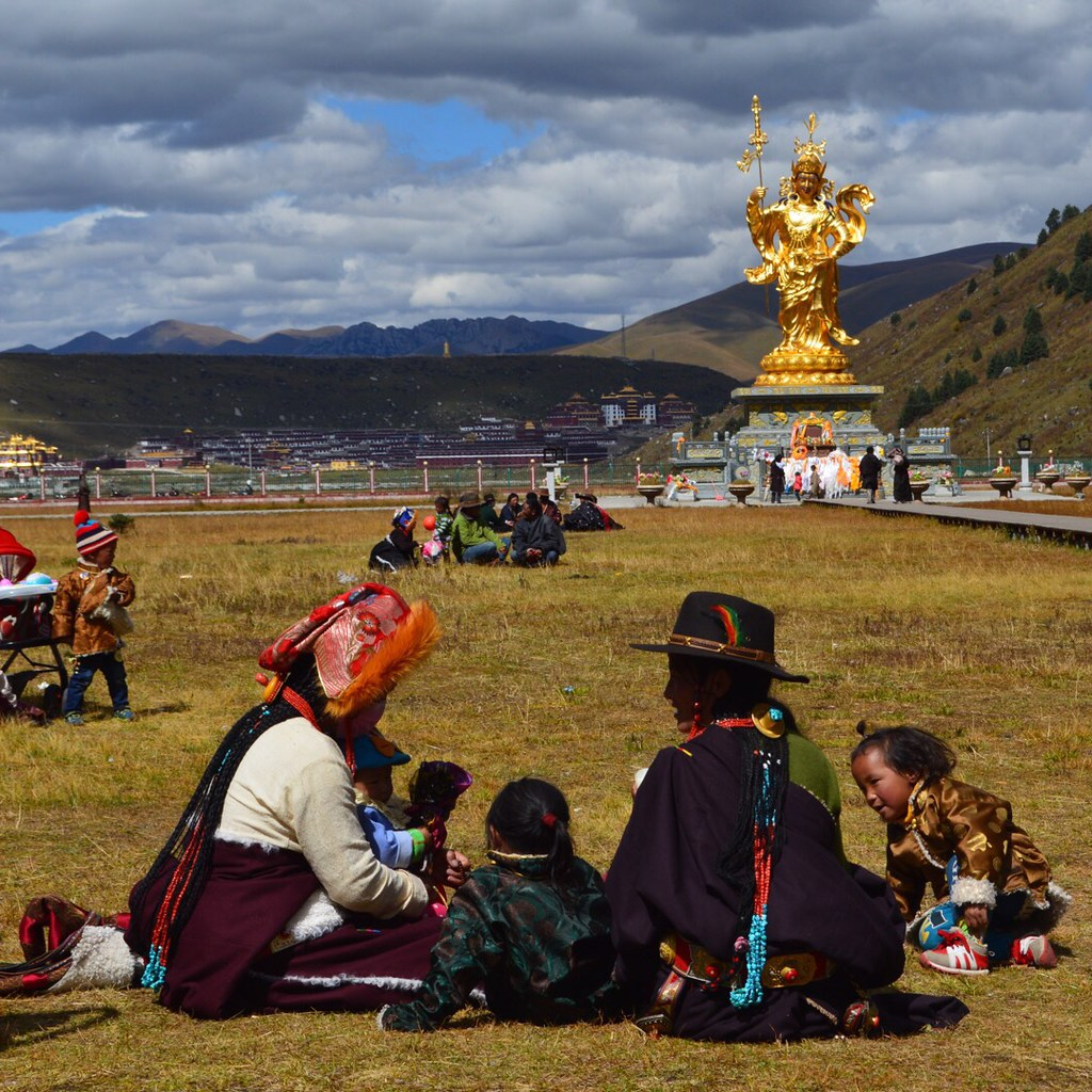Tibetans in front of a golden Buddha at the Golden Lotus Temple