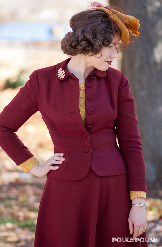 Fall outfit with a vintage 1940s wine red suit paired with a yellow feathered tilt hat and cabled sweater