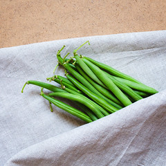 Green beans on a table with a napkin