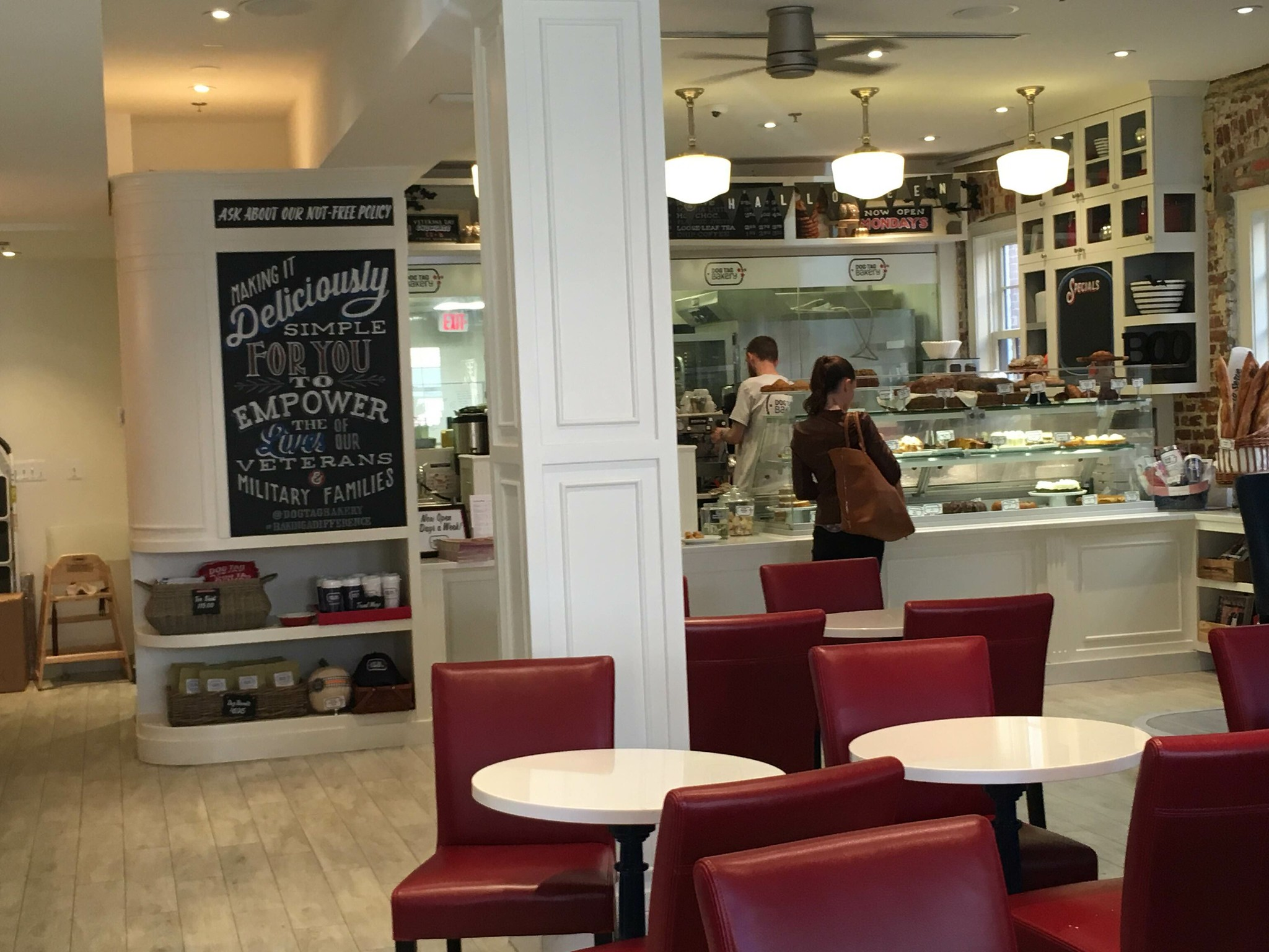 The inside of the bakery. There are white circular tables with red cushioned seats. A woman waits in front of a counter with a baked goods display. An employee works behind the counter.