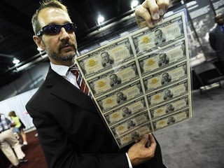 Kevin Brown with sheet of $100,000 bills