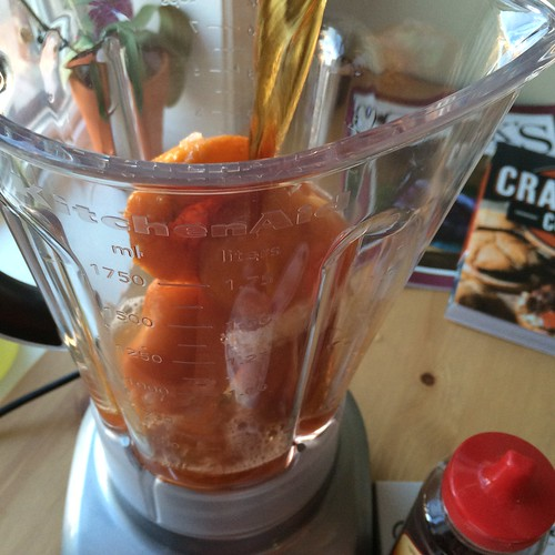 Peaches in a blender. Tea being poured over them.