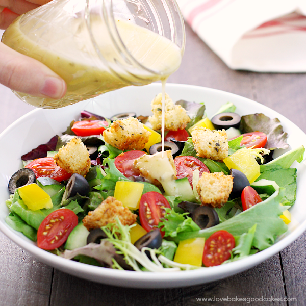Italian-Style Salad in a bowl with Italian dressing being poured over the top.