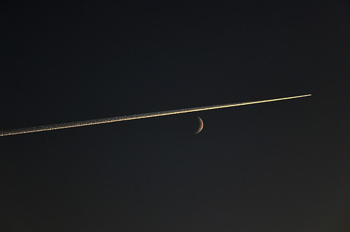Vapour trail left by a jet passing in front of the moon, St Petersburg, Russia