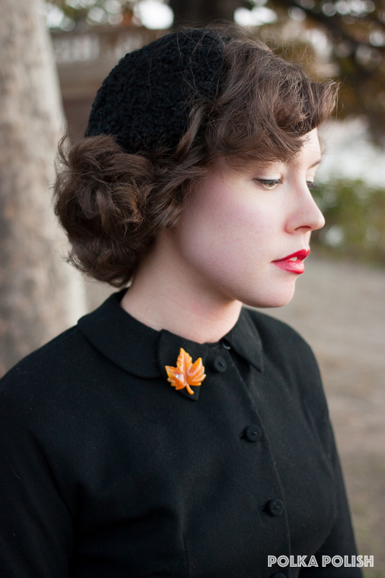 A vintage Avon maple leaf pin is a bright splash of fall color against a somber black ensemble