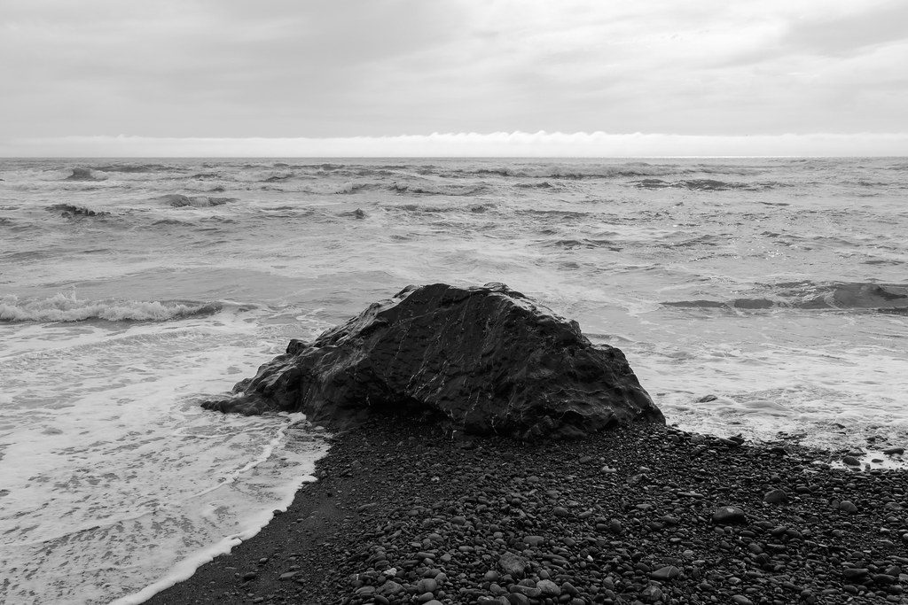 Waves wash over a rock on Crescent Beach in Jedediah Smith Redwoods State Park