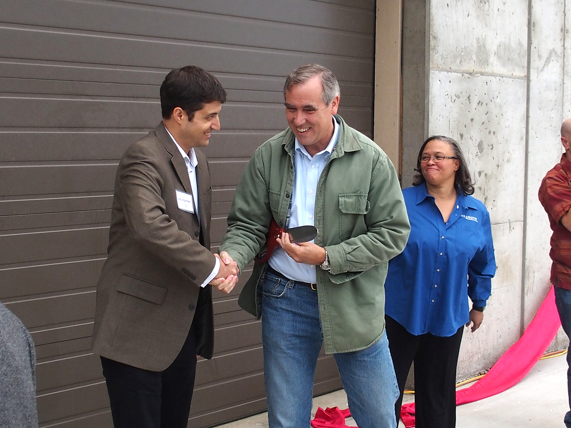 Following the ribbon cutting for Watson Hydropower Facility Jed Jorgensen, with the Energy Trust of Oregon congratulates U.S. Sen. Jeff Merkley while Deputy Commissioner Dionne Thompson looks on. Photo Credit: Energy Trust of Oregon