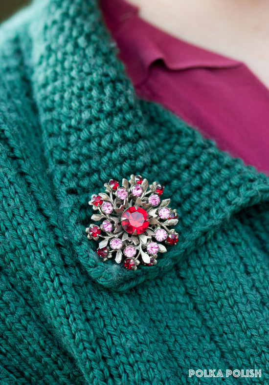 An atomic floral vintage brooch in sparkling red and pink cut glass stones adorns the collar of a green knit sweater