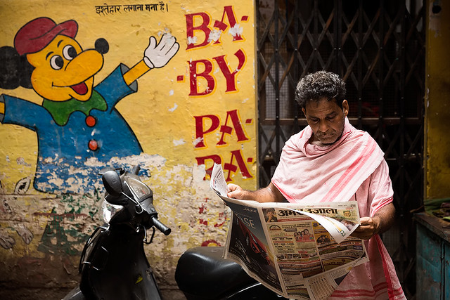 A man reading the newspaper in the streets of Varanasi, India.