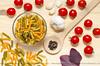 Pasta preparation: pasta, tomatoes, basil, garlic, black pepper.