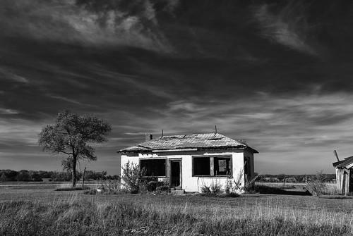 trees sky blackandwhite monochrome clouds shadows garage horizon neglected abandonedhouse oxidation weathered deterioration fadedpaint openwindows brokenroof unpaintedwood cloudsstormssunsetssunrises