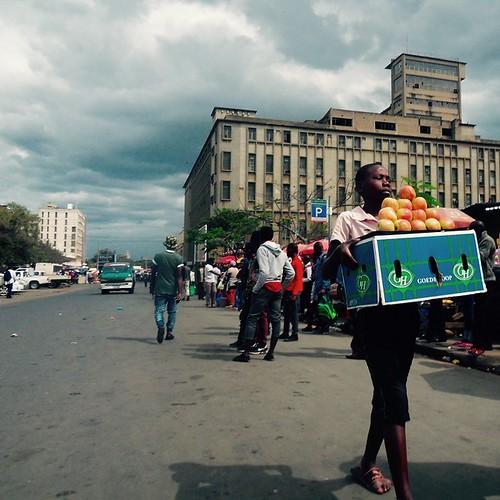 Maputon kadulla ihmisryhmä odottaa chapa-minibussin pysähtymistä ja myyjinä toimii myös lapsia.
