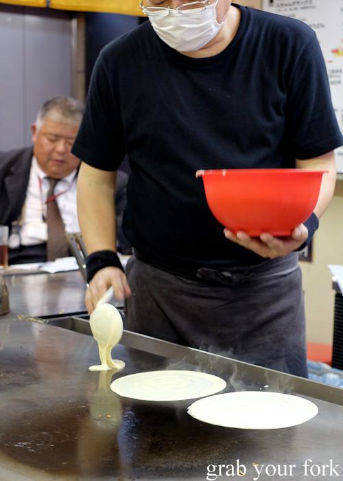 Ladling okonomiyaki batter at Okonomimura, Hiroshima