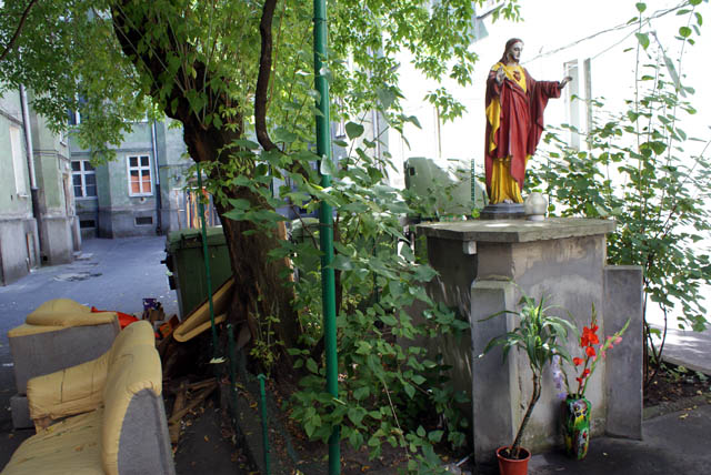 > Jésus en rouge et jaune à côté d'un canapé défoncé dans le quartier de Praga à Varsovie.