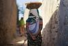 Ethiopian woman walking with head load and baby, Harar, Ethiopia