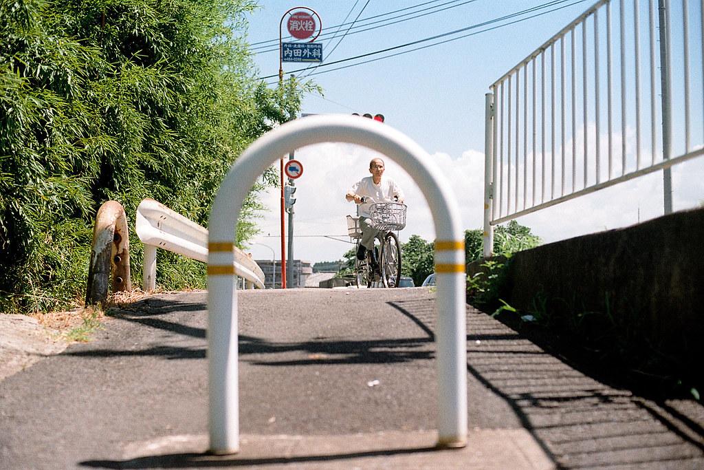 """千葉県佐倉市 さくらし 2015/08/05 在佐倉巷弄裡拍照,走到公路上有一個半圓的柵欄,和前面騎車過來的阿伯拍照,他好像有看到我在拍他。  當我在拍這個柵欄的時候,我也是遠遠的看到阿伯騎腳踏車經過,本來對焦在欄杆上面,快速移到後方他身上,如果仔細看上面的紅綠燈,可以發現阿伯他闖紅燈喔!  Nikon FM2 / 50mm Kodak ColorPlus ISO200  <a href=""""http://blog.toomore.net/2015/08/blog-post.html"""" rel=""""noreferrer nofollow"""">blog.toomore.net/2015/08/blog-post.html</a> Photo by Toomore"""