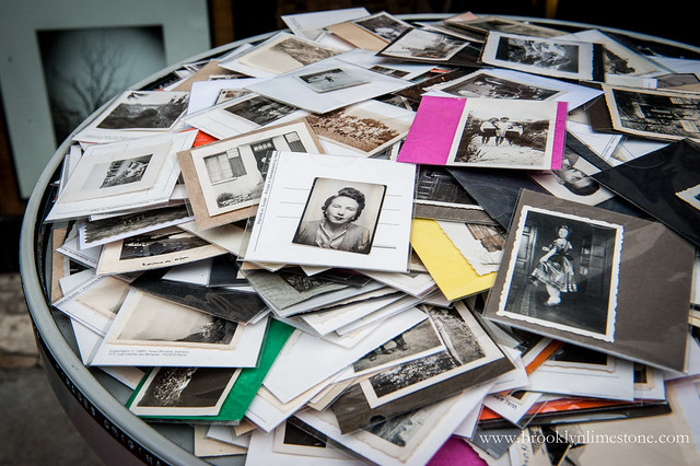 A stack of antique black and white photos for sale