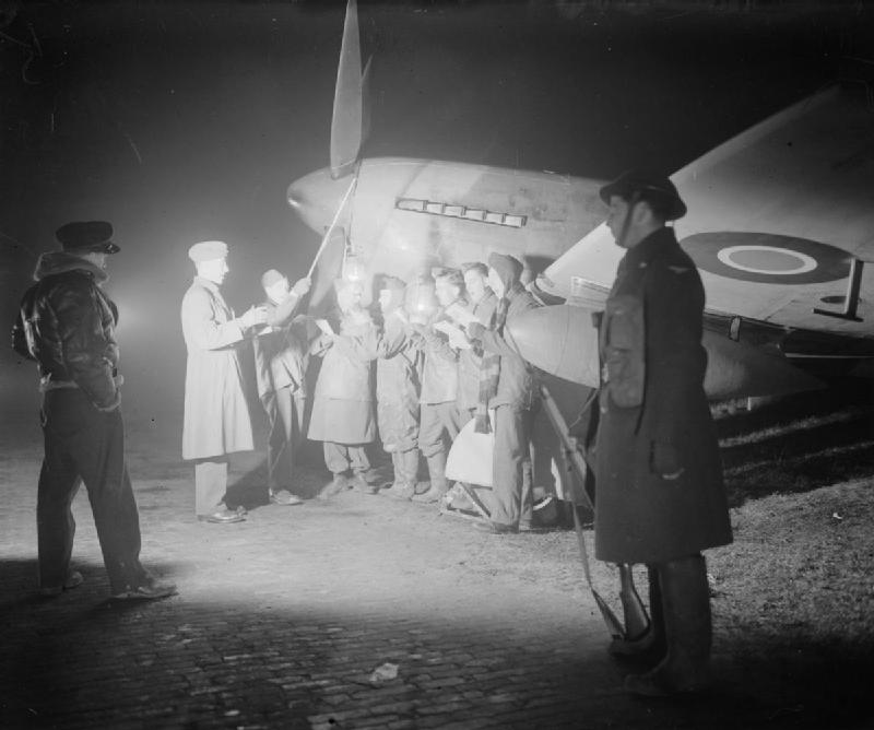 The ground crew of No. 122 Wing singing Christmas carols by a Hawker Tempest in a dispersal at Volkel airfield (B80), Holland 1944