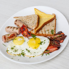 Breakfast setting with fried eggs, bacon, muesli,…