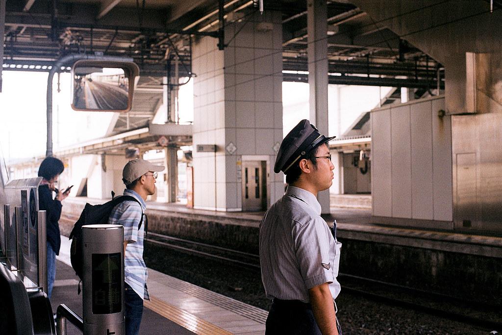 """列車長 八戶(Hachinohe) 前往岩手久慈 2015/08/08 下一班列車的列車長,他很專業的穩穩的站在月台上,而上一班列車誤點,不時的拿出時刻表出來對時。  Nikon FM2 / 50mm Kodak ColorPlus ISO200  <a href=""""http://blog.toomore.net/2015/08/blog-post.html"""" rel=""""noreferrer nofollow"""">blog.toomore.net/2015/08/blog-post.html</a> Photo by Toomore"""